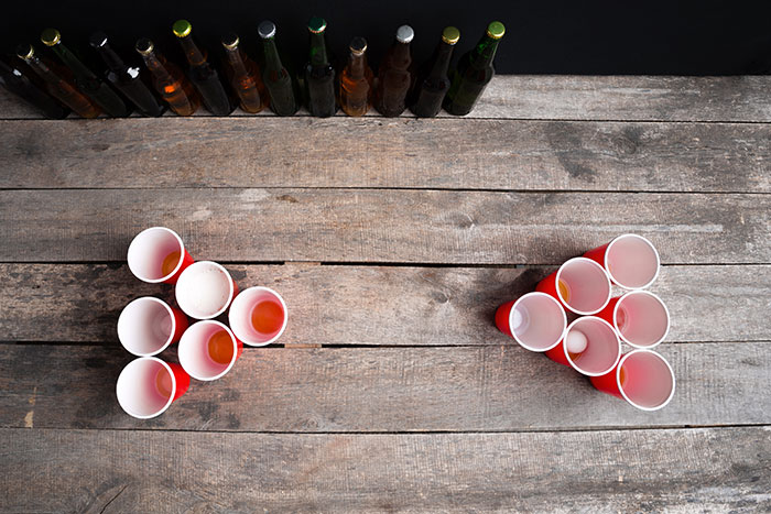 Beer pong setup with 6 cups on each side of the table in a pyramid shape with the tip pointing to the opposing team